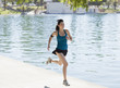 Woman running along lake in park