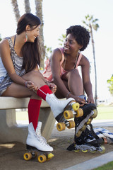 Women lacing up skates in park