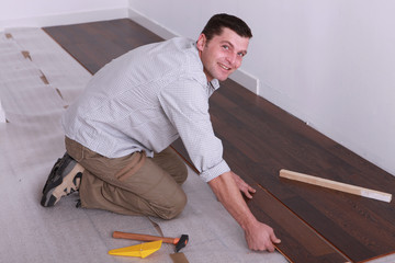 Man slotting laminate, flooring together