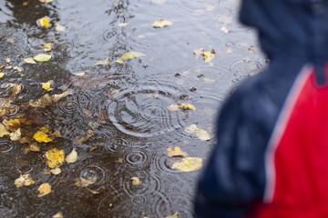 Girl watching rain drops in puddle