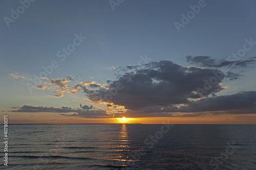 Sun setting over waves on beach