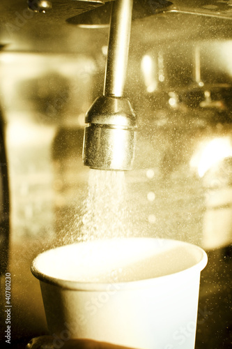 Water pouring from faucet into cup