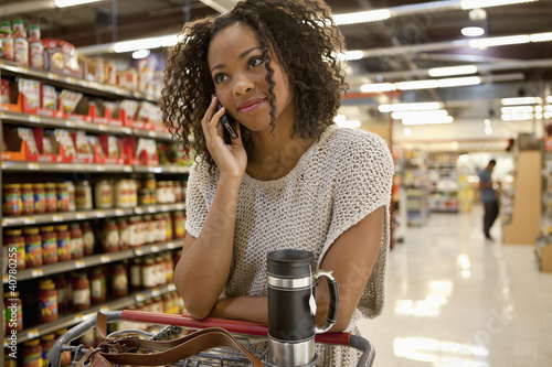 Woman talking on cell phone in supermarket