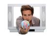 Man inside television holding globe