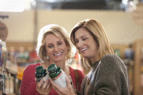 Women examining supplement bottles in store