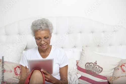 Older woman using tablet computer in bed