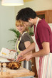 Couple preparing a meal together with the help of a cookbook