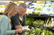 Couple checking grocery list in supermarket