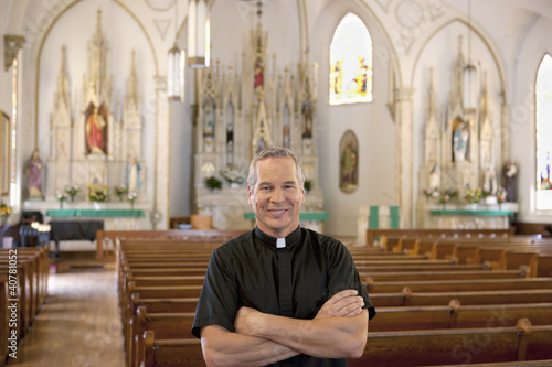 Priest smiling in ornate church