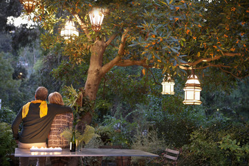 Couple relaxing in garden at twilight