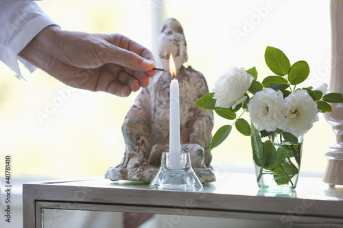 Man lighting candle in living room
