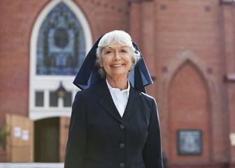 Smiling nun walking outdoors