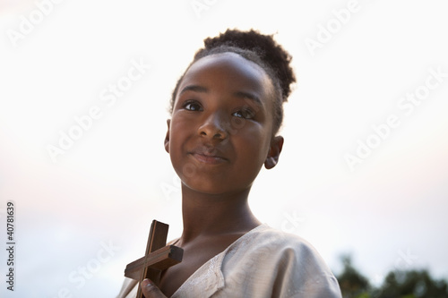 Smiling girl holding wooden cross