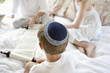 Boy wearing yarmulke and reading Torah scrolls