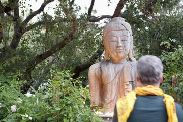 Older man examining Buddha statue