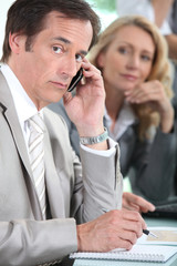 Male executive on cellphone during meeting