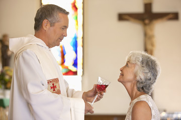 Priest giving communal wine to woman