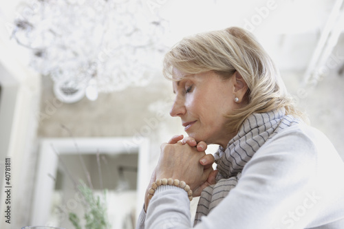 Older woman clasping hands in prayer