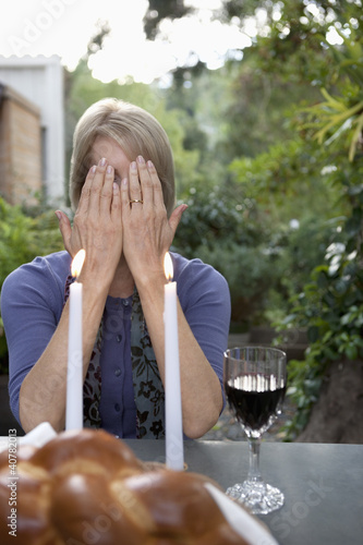 Woman covering her face at Sabbath dinner