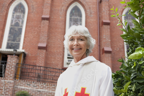 Smiling reverend standing outside church