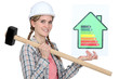 Woman holding energy rating information and sledge-hammer