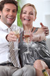 Couple sat down holding champagne glasses arms held out