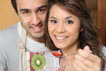 Young man feeding his girlfriend strawberries