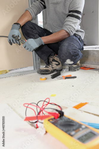 Electrician kneeling by voltmeter