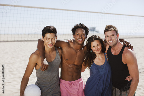 Friends hugging on beach volleyball court