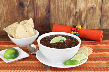 Black bean mexican soup with chips and lime.