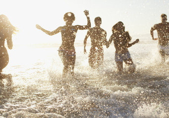 Friends playing in waves on beach