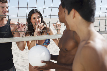 Friends playing beach volleyball together