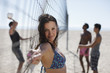 Woman leaning on beach volleyball net