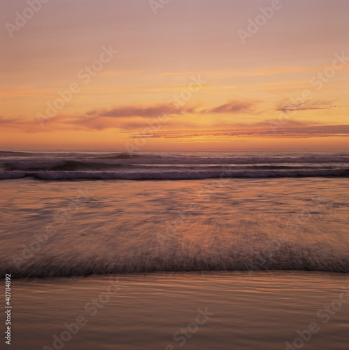 Waves rolling on beach at sunset