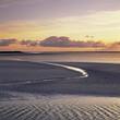 Water carving path through sandy beach