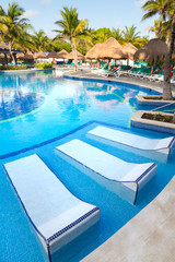 Tropical swimming pool with sunbeds in Mexico