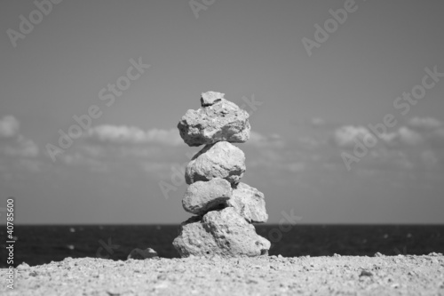 Astone stack against sea and blue sky