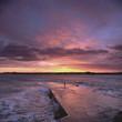 Waves crashing on concrete pier at sunset