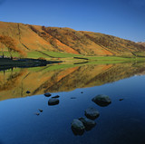 Rolling hills reflected in still lake