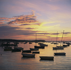 Empty boats in still harbor at sunset