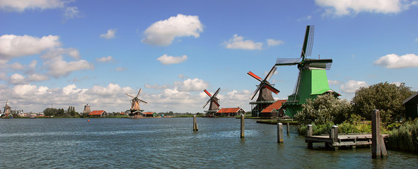 Panoramic view on river and windmills.