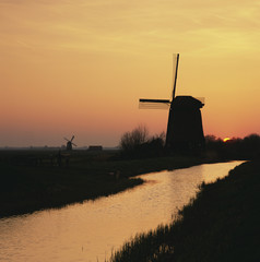 Silhouette of windmill and river in rural landscape