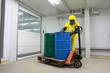 specialist working with barrels of toxic substance on forklift