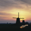 Silhouette of windmills in rural landscape