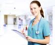 Smiling female medical doctor with clipboard in a corridor of a