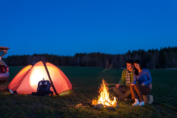 Tent camping car couple sitting by bonfire