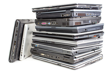Pile of used laptops, white background