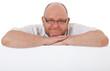Mann mittleren Alters hinter weißer Wand
