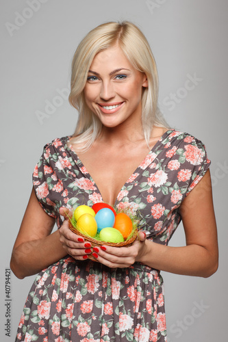 Portrait of female holding basket with Easter eggs