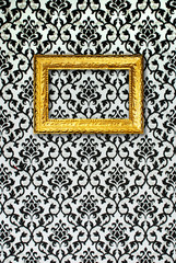 Gold frame on a black and white wallpaper